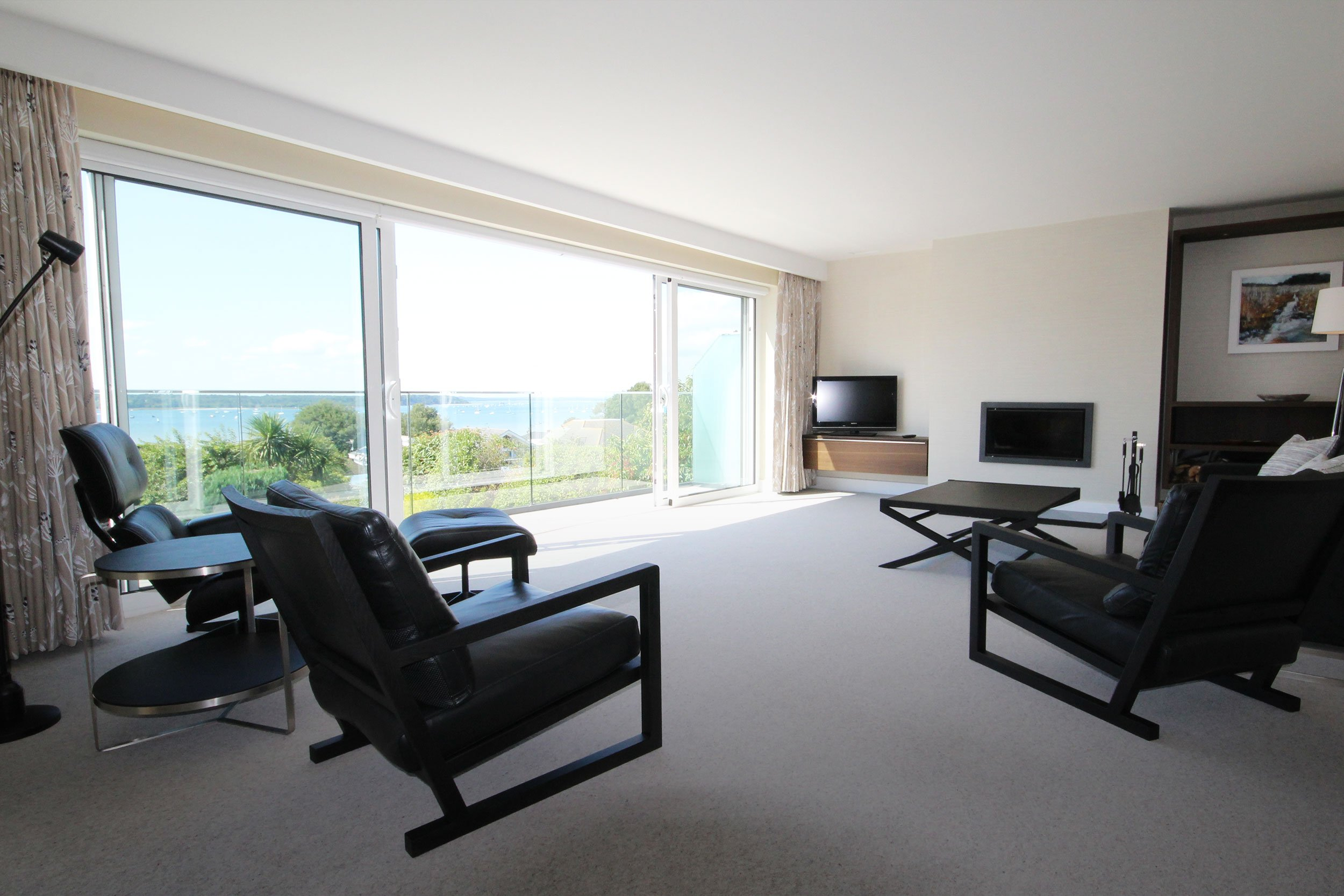 Modern living space leading to balcony with views of Sandbanks